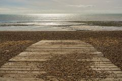 Beach and sea at Worthing, Sussex, England. Boarded ramp leading onto shingle beach at Goring in Worthing, West Sussex, England Royalty Free Stock Photos