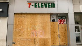 A boarded up 7-Eleven in Manhattan with graffiti following protests