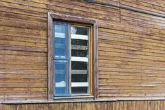 Boarded up window on weathered wooden wall. Boarded up and broken window on weathered wooden wall of abandoned old house royalty free stock photo