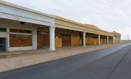 Boarded Up Shops of a Strip Mall on empty street. Boarded up and defunct strip mall in Niland, CA. Like in most communities around Salton Sea many streets show Stock Photos