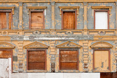 Boarded up derelict building facade peeling paint Royalty Free Stock Images
