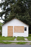 Boarded-up house. Small white house with plywood over window and door Stock Photos