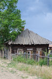 Boarded-up house. Abandoned old house beside the road under a tree Royalty Free Stock Image