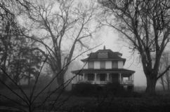 Boarded up house in the mist. Boarded up old abandoned house on a misty day gives it a haunted appearance stock photo