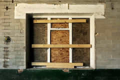 Boarded up window in a dereclit building Stock Photography