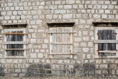 Boarded-up Windows in an old stone building stock image