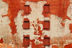 Boarded windows in old brick wall covered with red flaking plaster Stock Images
