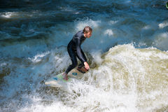 Boarders surfing on the Isar river in Munich, Bayern, Germany stock photo