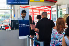 Boarding the aircraft. People at airport showing their boarding pass to a gate agent prior to boarding the aircraft Royalty Free Stock Photo