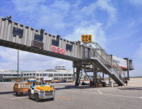 Boarding bridge with tow tractor on foreground on Beijing Capital International Airport. BEIJING-MAY 27. 2014. Boarding bridge with tow tractor on foreground on stock images