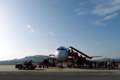 Boarding budget airline plane in rural Asia. A photograph showing travelers walking on the aircraft runway at a rural asian airport in Malaysia, on the tropical Stock Photography