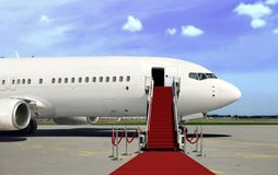 Boarding commercial  airplane with red carpet presentation. Over cloudy blue sky Stock Image