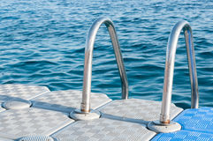 Boarding Ladder for Swimmers Mounted on a Plastic Floating Dock Stock Photos