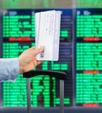 Boarding Pass at the airport. Close-up of woman showing banknotes at international airport with the flight information board background Stock Photo