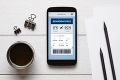 Boarding pass concept on smart phone screen with office objects. On white wooden table. All screen content is designed by me. Flat lay royalty free stock photos