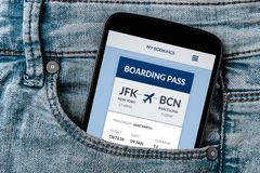 Boarding pass concept on smartphone screen in jeans pocket. All screen content is designed by me. Flat lay stock photo
