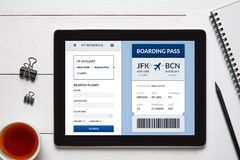 Boarding pass concept on tablet screen with office objects. On white wooden table. All screen content is designed by me. Flat lay royalty free stock photos