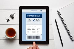 Boarding pass concept on tablet screen. With office objects on white wooden table. All screen content is designed by me. Flat lay stock photo