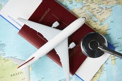 Medical travel concept. Boarding pass and a passport travel documents with medical stethoscope and airplane on world map background, close-up. Medical travel Stock Photo