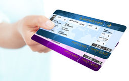 Boarding pass tickets holded by hand over white background. Two boarding pass tickets holded by hand over white background Royalty Free Stock Images