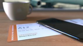 Boarding pass to Manchester and smartphone on the table in airport while travelling to the United Kingdom. 3D rendering. Boarding pass to Manchester and stock photos