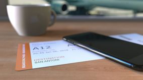 Boarding pass to San Antonio and smartphone on the table in airport while travelling to the United States. Boarding pass to San Antonio and smartphone on the stock footage