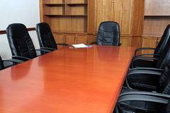 Boardroom. Black leather chairs around a boardroom table with files on the end Stock Image