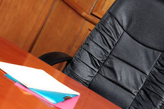 Boardroom chair. Black leather chair in a boardroom with files on the table Royalty Free Stock Photo