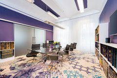 Boardroom with glass table and blue-violet walls Stock Image