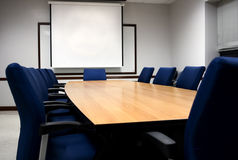 Boardroom presentation. Empty boardroom with a white presentation screen stock image