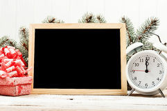 Boards for chalk with Christmas presents and white alarm clock Royalty Free Stock Photo