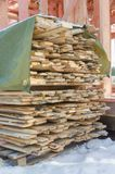 Boards near the house under construction. The boards folded in a stack, near the frame house under construction Stock Photo