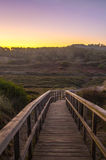 Boardwalk across the dunes at dawn. With mountains in the background Royalty Free Stock Image