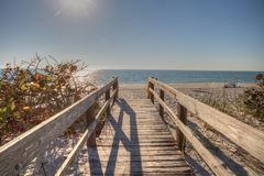 Boardwalk across the white sand beach of Delnor-Wiggins Pass Sta. Te Park with a blue sky above in Naples, Florida Royalty Free Stock Images