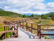 Boardwalk Arias port in Lapataia Bay in Terra del Fuego National. Boardwalk of Puerto Arias in Lapataia Bay with Andes mountains in background, Terra del Fuego stock images