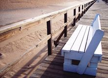 Boardwalk bench. A white bench on a boardwalk Royalty Free Stock Photos