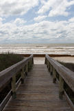 The boardwalk leading to the beach on a cloudy day Royalty Free Stock Images