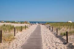 Boardwalk leading to beautiful white sand beach stock image