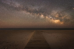 Boardwalk leading to the Milky Way Galaxy. A boardwalk leading to the ocean at Assateague Island National Seashore in Maryland Royalty Free Stock Photos