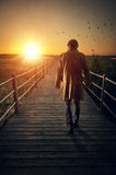 Boardwalk. A man with long coat walking in a boardwalk into de sunset Royalty Free Stock Images