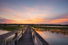 Boardwalk and marsh. The sun sets over the marsh and docks in Pawleys Island, South Carolina stock photos