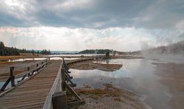 Boardwalk obok Kołtuniastej zatoczki i Czarnego wojownika Skacze prowadzący w Gorącego jezioro w Yellowstone parku narodowym w Wy Fotografia Royalty Free