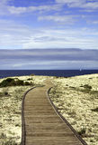 Boardwalk over sand dunes with blue sky and clouds Stock Photography