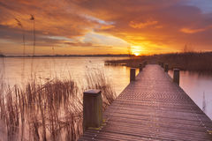 Boardwalk over water at sunrise in The Netherlands. Spectacular sunrise over a lake near Amsterdam in The Netherlands Stock Photos