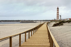 Boardwalk in Praia Barra with lighthouse Stock Photo