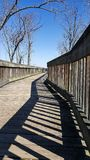 Boardwalk with shadows on sunny day. Boardwalk leading into the distance with interesting shadows and patterns and winter/early spring trees against a blue sky stock image