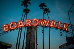 Boardwalk sign with lights and palm trees royalty free stock images