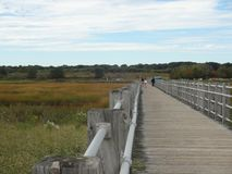 Boardwalk at Silver Sands State Park in Milford, CT. People walking in the distance on a boardwalk at Silver Sands State Park in Milford, CT Stock Images