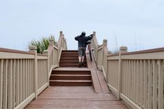 Boardwalk, Stairs, and Bike Ramp to the Beach. A woman pushing bike up a ramp on boardwalk and steps to the beach on Hilton Head Island, South Carolina Stock Images