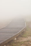 Boardwalk to... A wooden boardwalk disappears into the mist royalty free stock images